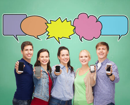 people, communication, school, advertisement and technology concept - smiling friends showing blank smartphones screens over blue background with doodles photo