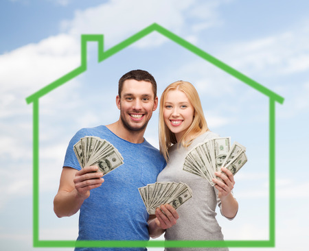 love, home, people and family concept - smiling couple holding dollar cash money over green house and blue sky background Foto de archivo