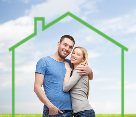 latin man: love, home, people and family concept - smiling couple hugging over green house and blue sky with grass background
