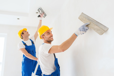 plastering: business, building, teamwork and people concept - group of smiling builders in hardhats with plastering tools indoors Stock Photo