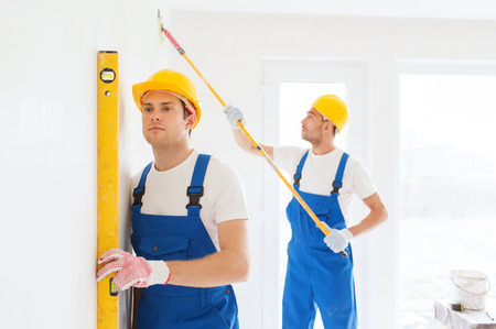 painter: building, teamwork and people concept - group of builders in hardhats with tools indoors