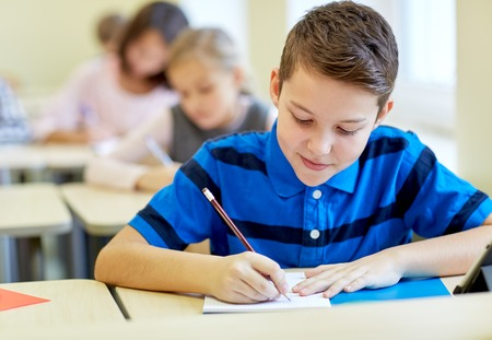 beautiful preteen girl: education, elementary school, learning and people concept - group of school kids with pens and notebooks writing test in classroom