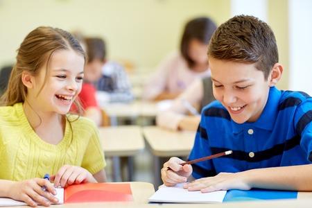 salon de clases: educación, escuela primaria, el aprendizaje y el concepto de la gente - grupo de niños de la escuela con lápices y cuadernos de escritura de prueba en el aula Foto de archivo