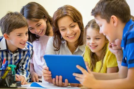 onderwijs, basisschool, onderwijs, technologie en mensen concept - groep schoolkinderen met leraar op zoek naar tablet-pc computer in de klas