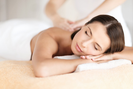 enjoying: health, beauty, resort and relaxation concept - beautiful woman with closed eyes in spa salon getting massage