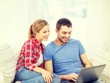 home, technology and relationships concept - smiling couple with laptop computer at home photo