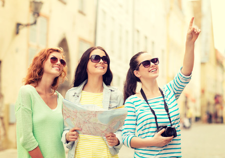 toerisme, reizen, vrije tijd, vakantie en vriendschap concept - lachende tienermeisjes met kaart en camera buiten Stockfoto