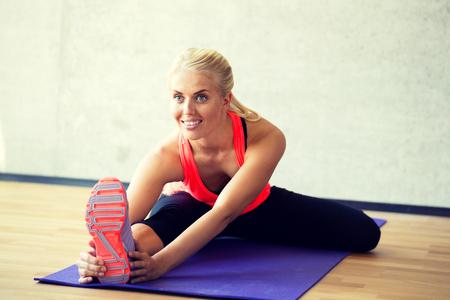 フィットネス、スポーツ、トレーニングやライフ スタイル コンセプト - ジムのマットで演習を行って女性を笑顔