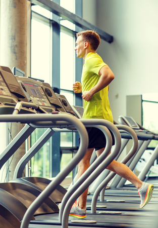treadmill: sport, fitness, lifestyle, technology and people concept - smiling man exercising on treadmill in gym