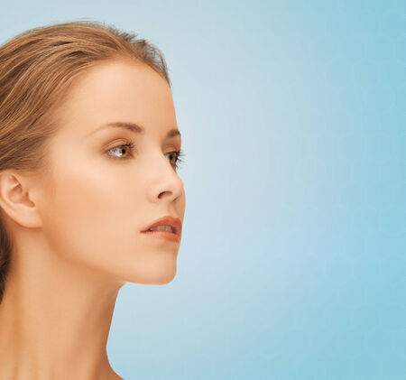 beauty, people and health concept - beautiful young woman face over blue background Stock Photo