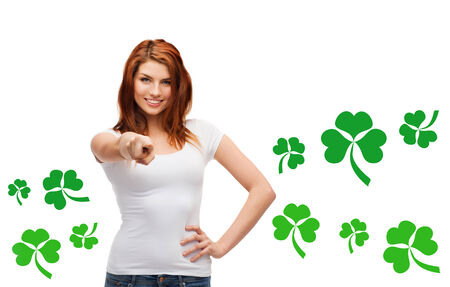 st  patricks day: gestures, holidays, st. patricks day and people concept - happy teenager in blank white t-shirt pointing at you over white background with green shamrock or clover