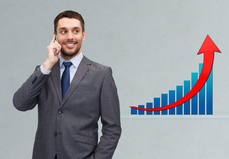business, technology, people, success and development concept - young smiling businessman calling on smartphone over gray background and growth chart photo