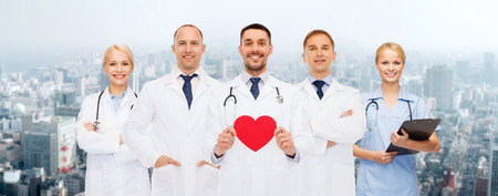 medics: medicine, profession, teamwork and healthcare concept - group of smiling medics or doctors holding red paper heart shape, clipboard and stethoscopes over city background