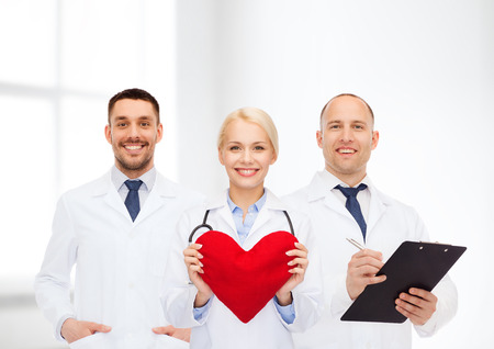 doctors smiling: healthcare, people and medicine concept - group of smiling doctors with heart and clipboard over clinic background Stock Photo