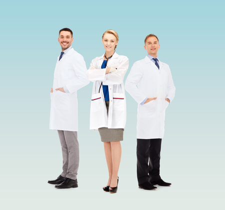 white coats: healthcare, profession and medicine concept - group of smiling doctors in white coats over blue background
