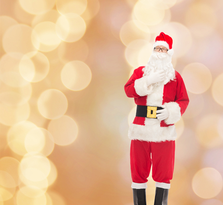 st nick: christmas, holidays and people concept - man in costume of santa claus over beige lights background Stock Photo