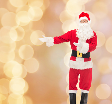 st nick: christmas, holidays, gesture and people concept - man in costume of santa claus over beige lights background