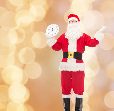 reminding: christmas, holidays and people concept - man in costume of santa claus with clock showing twelve over beige lights background