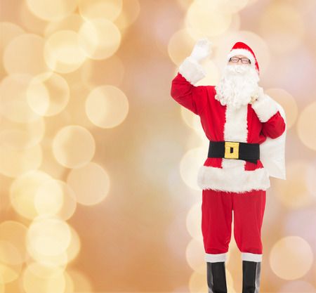 christmas, holidays, gesture and people concept - man in costume of santa claus with bag waving hand over beige lights background photo