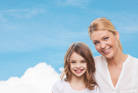 family, childhood, happiness and people - smiling mother and little girl over blue sky and white cloud background photo