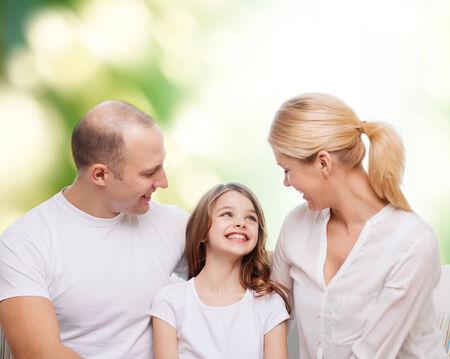 madre e hija adolescente: la familia, la infancia, la ecología y la gente - sonriente madre, el padre y la niña sobre fondo verde