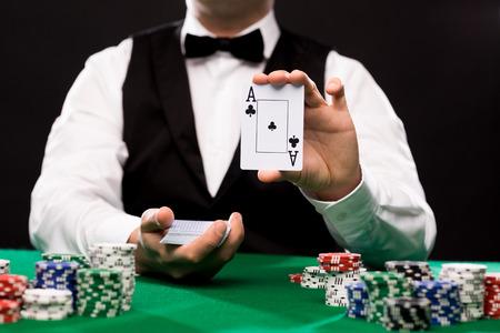 casino, gokken, poker, mensen en entertainment concept - close-up van holdem dealer met speelkaarten en chips op de groene tafel