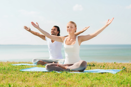 team lotus: fitness, sport, friendship and lifestyle concept - smiling couple making yoga exercises sitting on mats outdoors