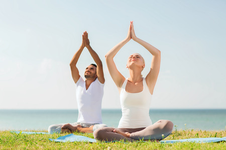 yoga beach: fitness, sport, friendship and lifestyle concept - smiling couple making yoga exercises sitting on mats outdoors