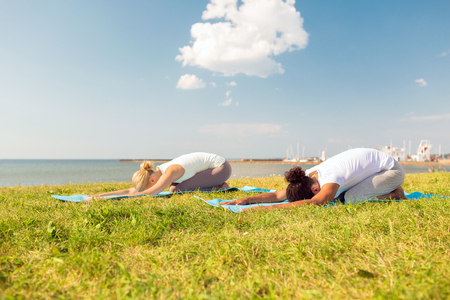 yoga beach: fitness, sport, people and lifestyle concept - couple making yoga exercises on mats outdoors