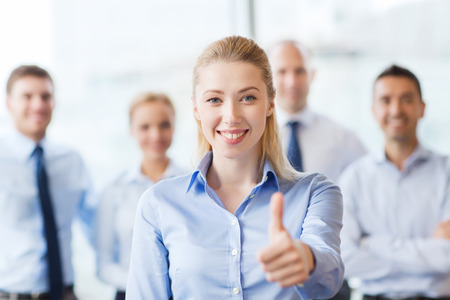 thumbs up man: business, people, gesture and teamwork concept - smiling businesswoman showing thumbs up with group of businesspeople in office