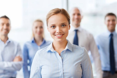 business partner: business, people and teamwork concept - smiling businesswoman with group of businesspeople in office