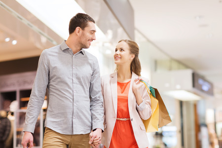 consumerism: sale, consumerism and people concept - happy young couple with shopping bags walking and talking in mall