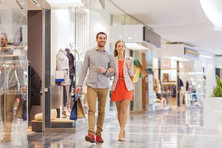 consumerism: sale, consumerism and people concept - happy young couple with shopping bags walking in mall