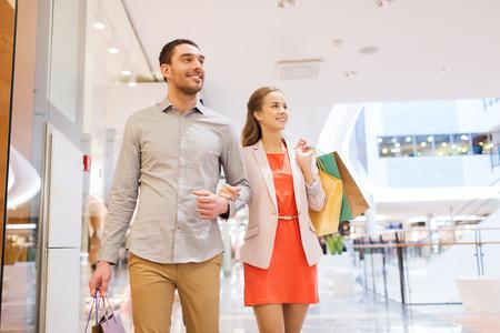 jovenes felices: venta, el consumismo y el concepto de la gente - la feliz pareja joven con bolsas de compras caminando en mall