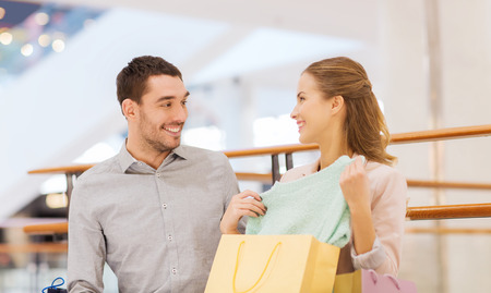 consumerism: sale, consumerism and people concept - happy young couple showing content of shopping bags in mall