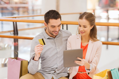 consumerism: sale, consumerism, leisure and people concept - happy couple with tablet pc computer, credit card and shopping bags in mall