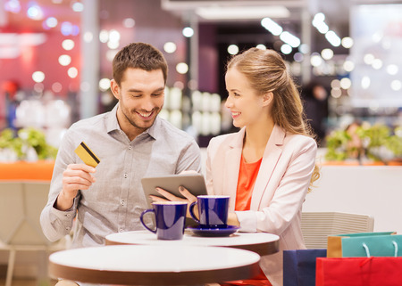 shopping centre: sale, shopping, consumerism, leisure and people concept - happy couple with tablet pc and credit card drinking coffee in mall