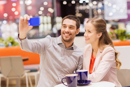 consumerism: sale, shopping, consumerism, technology and people concept - happy young couple with smartphone taking selfie at cafe in mall