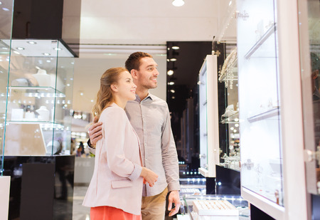 sale, consumerism and people concept - happy couple looking to shopping window at jewelry store in mall