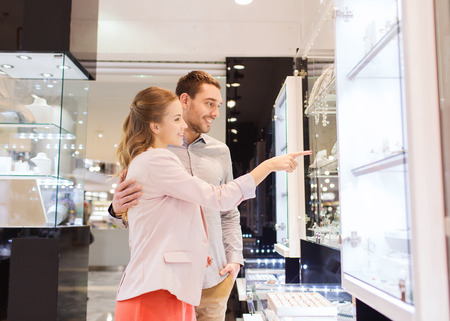 consumerism: sale, consumerism and people concept - happy couple pointing finger to shopping window at jewelry store in mall