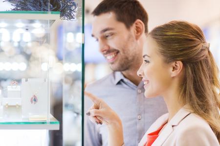 販売、消費者と人々 のコンセプト - 幸せなカップルをジュエリー ショッピング ウィンドウに指を指すストア モール