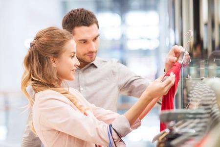 Venta, el consumismo y el concepto de la gente - joven pareja feliz con bolsas de la compra que eligen la alineada en el centro comercial Foto de archivo - 35196008
