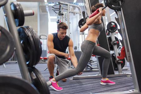 levantando pesas: deporte, gimnasio, trabajo en equipo, levantamiento de pesas y el concepto de la gente - hombre joven y entrenador personal con mancuerna flexionar los músculos en el gimnasio Foto de archivo
