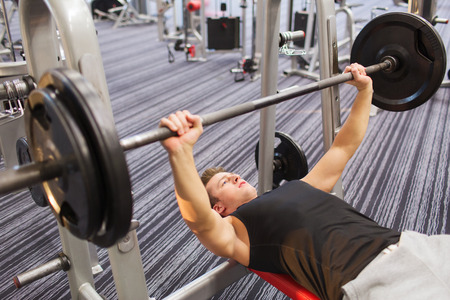 barbell: sport, bodybuilding, lifestyle and people concept - young man with barbell flexing muscles and making bench press in gym
