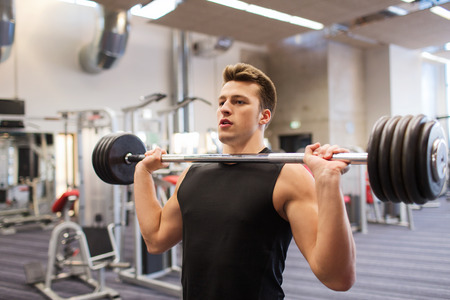 sport, bodybuilding, lifestyle and people concept - young man with barbell flexing muscles in gym Foto de archivo