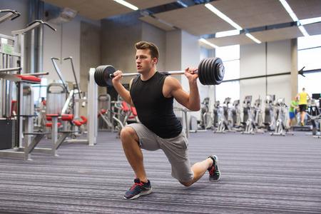 スポーツ、ボディービル、ライフ スタイル、人々 の概念 - バーベル筋肉を屈曲とジムで突進を押して肩を作ると若い男 写真素材