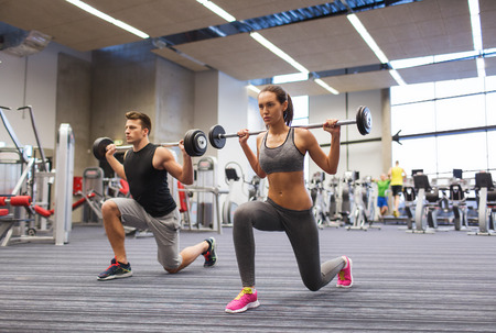 man holding: sport, bodybuilding, lifestyle and people concept - young man and woman with barbell flexing muscles and making shoulder press lunge in gym