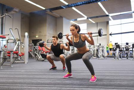 atleta: deporte, culturismo, estilo de vida y concepto de la gente - hombre joven y una mujer con mancuerna de flexionar los m�sculos y hacer press de hombros en cuclillas en el gimnasio