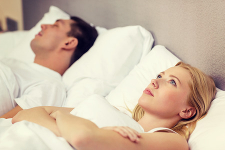husbands and wives: hotel, travel, relationships, and problems with sleep concept - family couple in bed, woman with insomnia Stock Photo