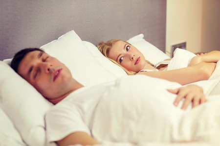 family problems: hotel, travel, relationships, and problems with sleep concept - family couple in bed, woman with insomnia Stock Photo